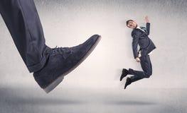 Kleine zakenman die door grote schoen wordt geschopt stock afbeeldingen
