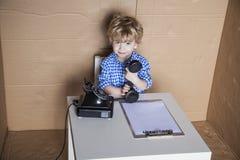 Kleine zakenman die een telefoon in zijn hand, de situatie weg houden stock fotografie
