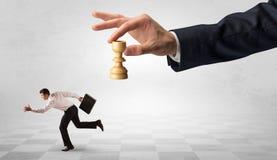 Kleine zakenman die vanaf grote hand met schaakstukconcept lopen royalty-vrije stock afbeeldingen