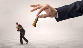 Kleine zakenman die vanaf grote hand met schaakstukconcept lopen stock afbeelding