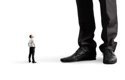 Kleine zakenman die zijn grote werkgever bekijken Royalty-vrije Stock Fotografie