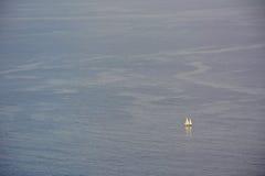 Kleine zeilboot op de oceaan stock afbeelding