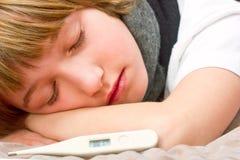 Kleine zieke jongen die op bed met digitale thermometer liggen Stock Afbeeldingen