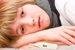 Kleine zieke jongen die op bed met digitale thermometer liggen Royalty-vrije Stock Afbeeldingen