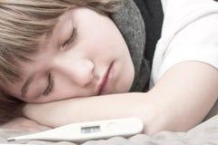 Kleine zieke jongen die op bed met digitale thermometer liggen Stock Afbeelding