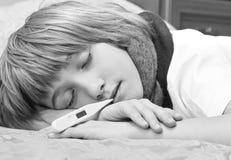 Kleine zieke jongen die op bed met digitale thermometer liggen Stock Fotografie