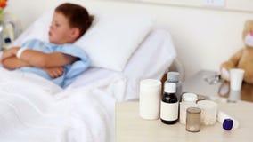 Kleine zieke jongenszitting in bed met geneeskunde in voorgrond stock footage