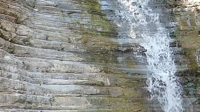 Kleine zuivere waterval op steenmuur Schone waterdaling van oude rotsen stock footage