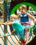 Kleine zusters bij speelplaats in park Royalty-vrije Stock Foto