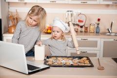 Kleine zusters die koekjes voorbereiden en zoeken voor Royalty-vrije Stock Afbeelding