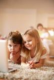 Kleine zusters die op de vloer bij woonkamer liggen en l gebruiken Royalty-vrije Stock Fotografie