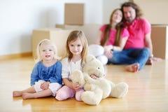 Kleine zusters en hun ouders in nieuw huis Stock Fotografie