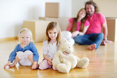 Kleine zusters en hun ouders in nieuw huis Stock Foto