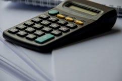 Kleine zwarte calculator op een lichte achtergrond royalty-vrije stock afbeelding