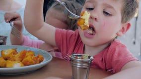 Kleine Zwillinge isst Nuggets der Gabel gebratenes Hühnermit Soße, Junge und Mädchen essen appetitanregendes im Restaurant zu Abe stock video footage