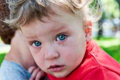 Kleinen Jungen, der an ihrer Mutter in ihren Armen schreit Lizenzfreie Stockfotografie