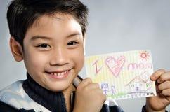 Kleiner asiatischer Junge, der Bild wiith Wort hält Stockbild