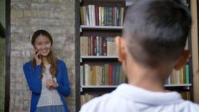 Kleiner asiatischer Junge, der mit junger Mutter durch intelligente Uhr und Betrieb mit ihr, dem Lächeln, den Buchregalen und Bac stock video