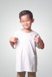 Kleiner asiatischer Junge, der sein weißes Hemd zeigt Stockfotografie