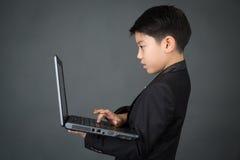 Kleiner asiatischer Junge im schwarzen Anzug mit Laptop Lizenzfreies Stockbild