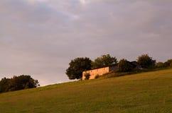 Kleiner Bauernhof auf Hügel am Sonnenaufgang Lizenzfreie Stockfotografie