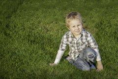 Kleiner blonder Junge auf dem Gras Lizenzfreie Stockfotografie