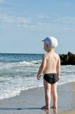 Kleiner blonder Junge auf dem Strand, der die Wellen betrachtet Stockfotos