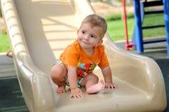 Kleiner blonder Junge auf einem Dia im Park Stockbilder