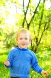 Kleiner blonder Junge auf grünem Laubhintergrund Lizenzfreie Stockbilder
