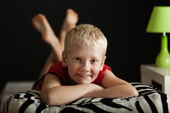 Kleiner blonder Junge auf Zebra kopiertem Kissen Lizenzfreies Stockbild