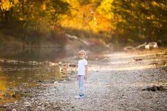 Kleiner blonder Junge in den grünen Gläsern, die auf dem Flussufer spielen Herbst im gelben Wald Stockbild