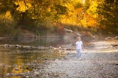 Kleiner blonder Junge in den grünen Gläsern, die auf dem Flussufer spielen Herbst im gelben Wald Lizenzfreie Stockbilder