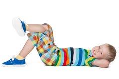 Kleiner blonder Junge, der auf dem Boden stillsteht Stockbild