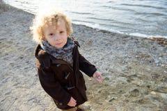 Kleiner blonder Junge, der auf dem Strand eintägiger Herbst spielt Lizenzfreie Stockfotos