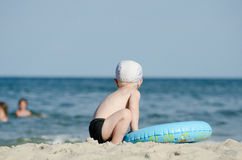 Kleiner blonder Junge, der auf der Küste mit einem Schwimmenkreis mit seinem zurück sitzt Lizenzfreies Stockfoto