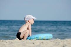 Kleiner blonder Junge, der auf der Küste mit einem Schwimmenkreis sitzt Stockfotos