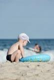 Kleiner blonder Junge, der auf der Küste mit einem Schwimmenkreis sitzt Stockbilder