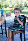 Kleiner blonder Junge, der auf Hochstuhl im Café mit Cocktail sitzt Lizenzfreie Stockfotos