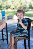 Kleiner blonder Junge, der auf Hochstuhl im Café mit Cocktail sitzt Stockfotos