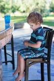 Kleiner blonder Junge, der auf Hochstuhl im Café mit Cocktail sitzt Lizenzfreies Stockbild
