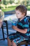 Kleiner blonder Junge, der auf Hochstuhl im Café mit Cocktail sitzt Lizenzfreie Stockbilder