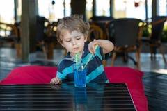Kleiner blonder Junge, der auf Hochstuhl im Café mit Cocktail sitzt Stockfotografie