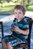 Kleiner blonder Junge, der auf Hochstuhl im Café mit Cocktail sitzt Stockbilder