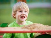 Kleiner blonder Junge, der auf Spielplatz spielt Stockfotografie