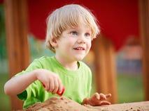 Kleiner blonder Junge, der auf Spielplatz spielt Stockbilder