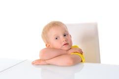 Kleiner blonder Junge, der bei Tisch auf Stuhl sitzt Stockfotografie