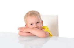 Kleiner blonder Junge, der bei Tisch auf Stuhl sitzt Stockfotos