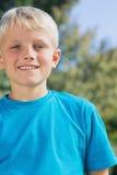 Kleiner blonder Junge, der an der Kamera lächelt Lizenzfreie Stockfotografie