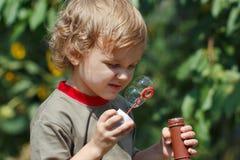 Kleiner blonder Junge, der draußen mit Luftblasen spielt Stockbild