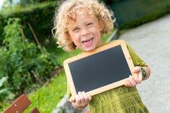 Kleiner blonder Junge, der eine Tafel hält Lizenzfreie Stockbilder